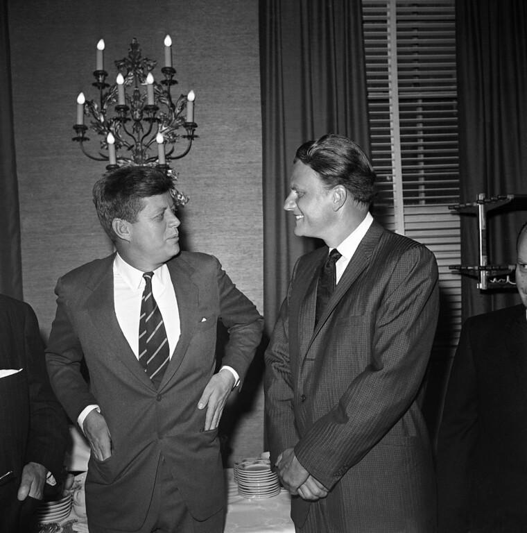". President John F. Kennedy talks with evangelist Billy Graham at the annual \""Presidential Prayer Breakfast\"" in a Washington hotel, Feb. 9, 1961.  (AP Photo)"