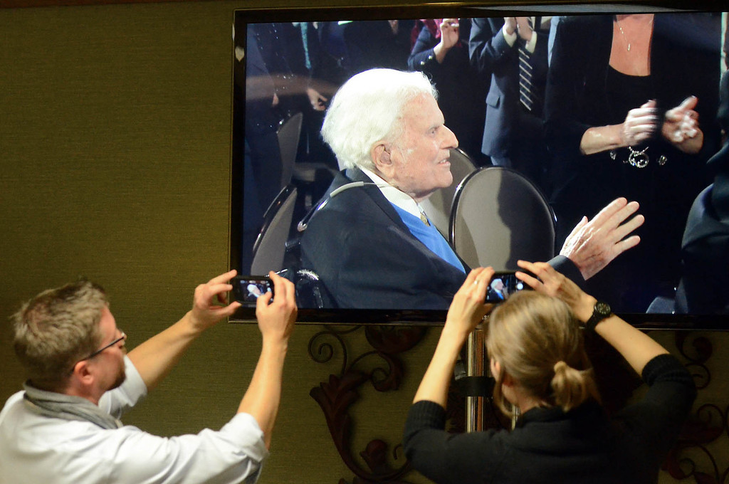 . Journalists photograph a television monitor in the media room at the Grove Park Inn as Billy Graham arrives for a celebration of his 95th birthday in Asheville, N.C., Thursday, Nov. 7, 2013.  (AP Photo/The Charlotte Observer, Todd Sumlin)