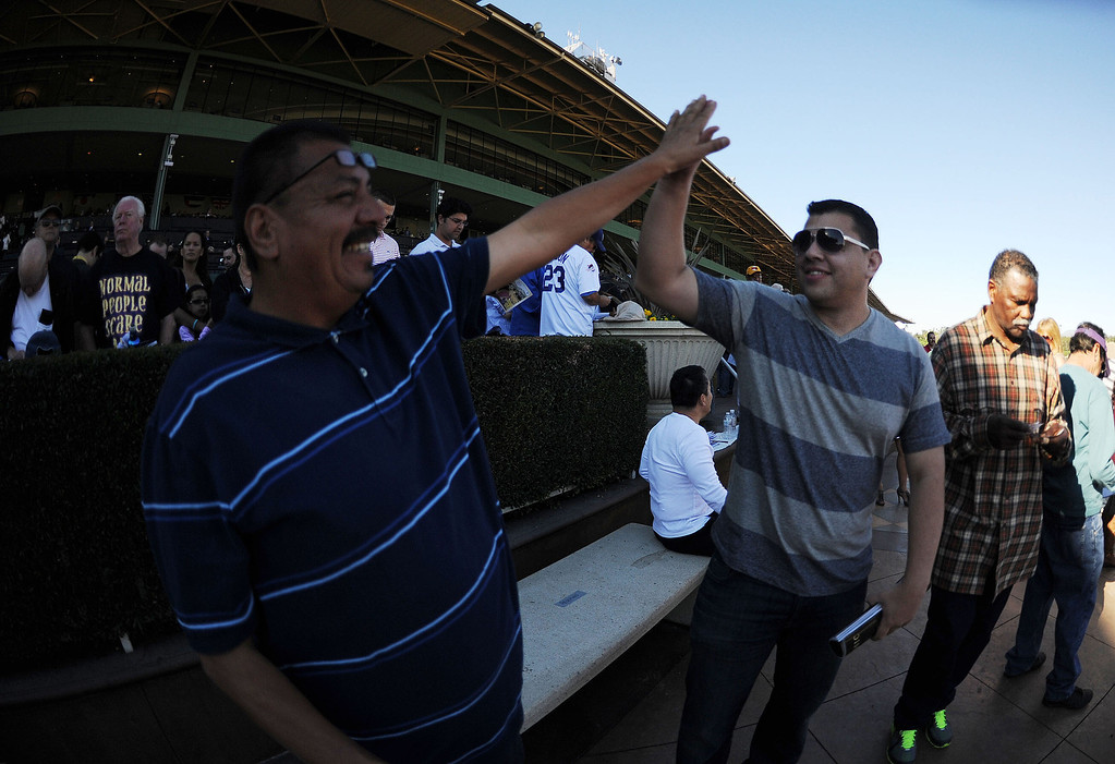 . Fans react after winning in the first race of the day during the Breeders\' Cup at Santa Anita Park in Arcadia, Calif., on Saturday, Nov. 2, 2013. 