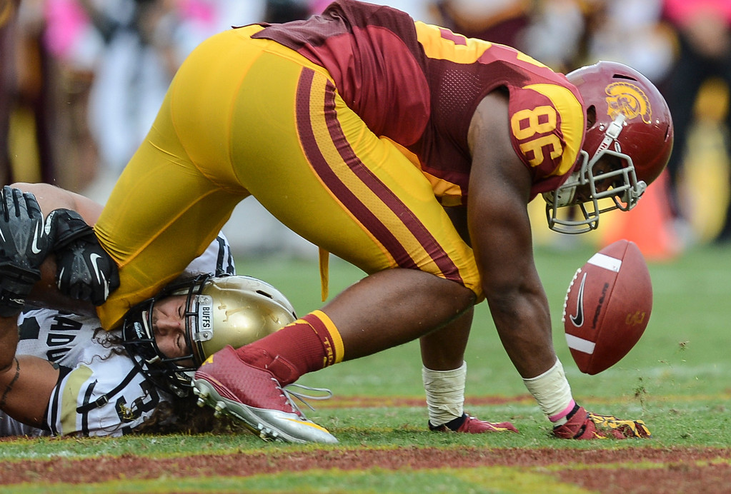 . USC\'s Xavier Grimble fumbles the ball as his is brought down by Colorado\'s Jon Major Saturday.  USC defeated Colorado 50-6.  (10/20/12) Photo by David Crane/L.A. Daily News
