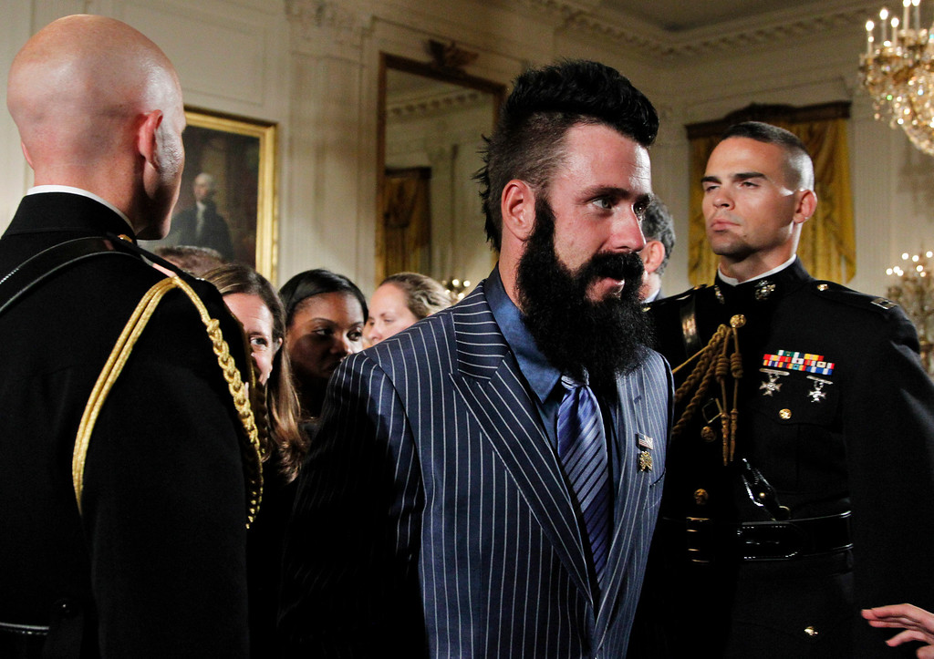 . San Francisco Giants pitcher Brian Wilson, center, walks past Marine honor guards at the conclusion of a ceremony hosted by President Barack Obama in the East Room of the White House in Washington, honoring the 2010 World Series baseball champions Monday, July 25, 2011.  (AP Photo/Manuel Balce Ceneta)