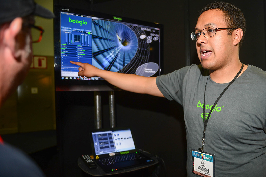 . Jose Torres, right, explains the display data from his Boogio, a tech product worn in shoes, at Electronic Entertainment Expo in Los Angeles on Tuesday, June 10, 2014. (Photo by Watchara Phomicinda)