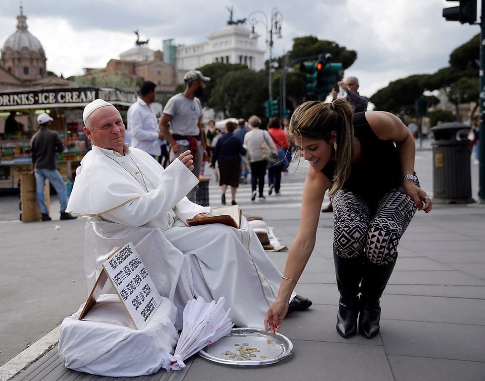 . A tourist drops a coins near Plisko Julius, from Slovakia, impersonating late Pope John Paul II, after posing with him for a souvenir picture in Rome, Wednesday, April 23, 2014. Hundred thousands of pilgrims and faithful are expected to reach Rome to attend the scheduled April 27 ceremony at the Vatican in which Pope Francis will elevate in a solemn ceremony John XXIII and John Paul II to sainthood. (AP Photo/Gregorio Borgia)