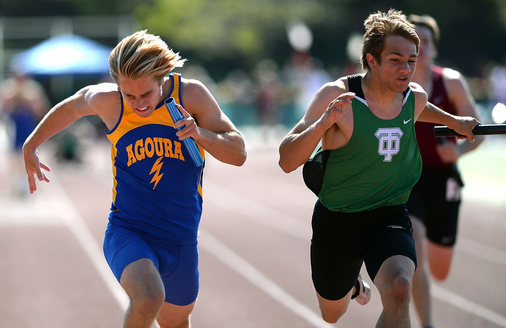 . Agoura High School\'s Christian Williams and Thousand Oaks\' Stephen Hernandez run the anchor leg during the 4X100 relay during the Marmonte League track and field finals May 9, 2014 in Moorpark.(Andy Holzman/Los Angeles Daily News)