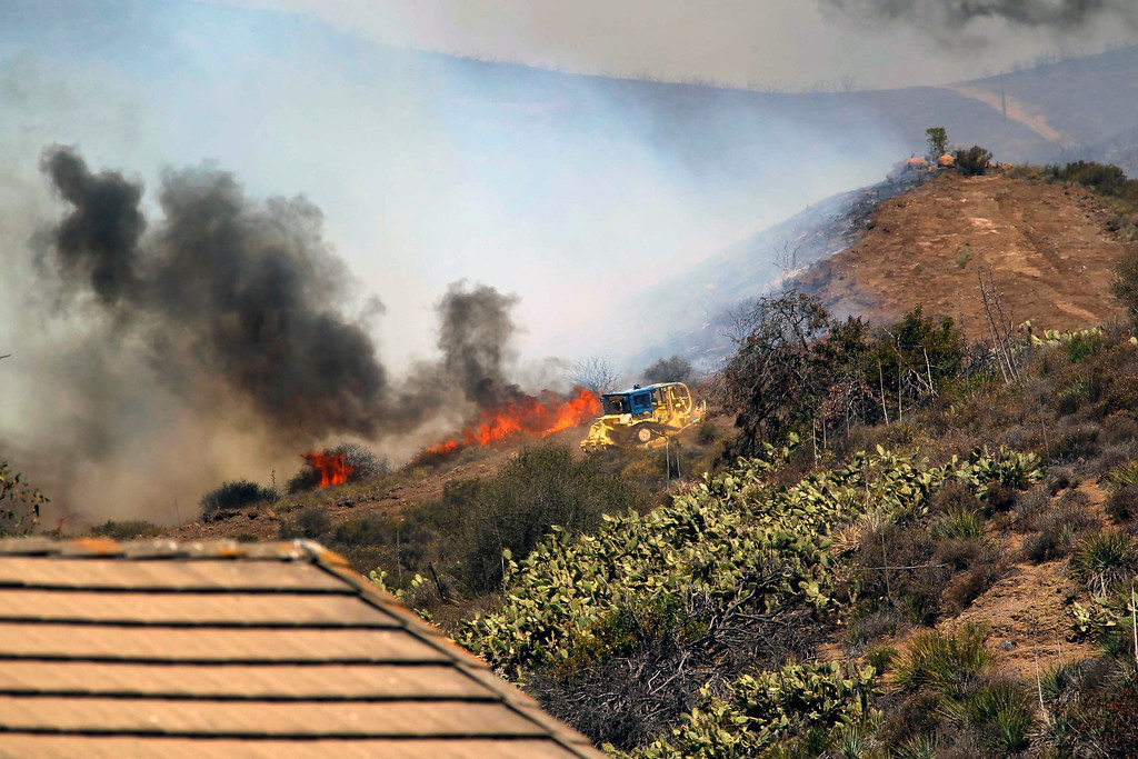 . A bulldozer helps clear a hill near a fire in Thousand Oaks, Calif. on Thursday, May 2, 2013. A 2,000-acre blaze that began in the Camarillo area along U.S. 101 in Ventura County was uncontained. It prompted the evacuation of a Thousand Oaks neighborhood and the campus of California State University, Channel Islands. At least a half-dozen RVs burned in a parking area enclosed by brushy hills. Embers scattered along ridges and into neighborhoods abutting the brush lands and smoke streamed for miles. More than 200 firefighters were aided by water- and fire retardant-dropping aircraft. (AP Photo/Nick Ut)