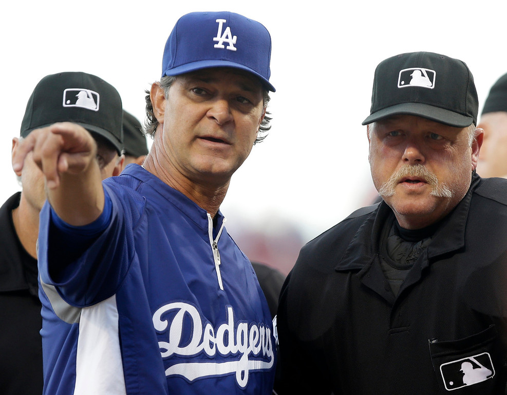 . Los Angeles Dodgers manager Don Mattingly, left, goes over the ground rules with home plate umpire Jim Joyce prior to a baseball game against the Cincinnati Reds, Friday, Sept. 6, 2013, in Cincinnati. (AP Photo/Al Behrman)