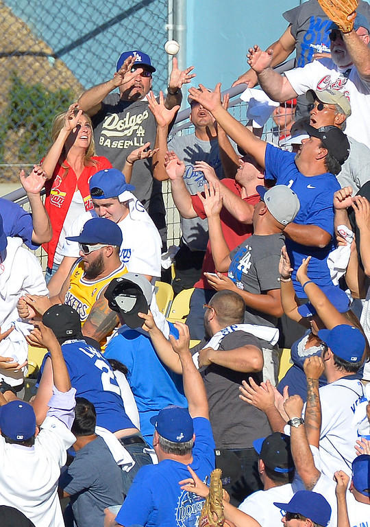 . Fans reach for the Andrian#23 Gonzalez homer in the 8th inning. The Dodgers played the Saint Louis Cardinals in game 5 of the National League Championship Series at Dodger Stadium in Los Angeles, CA. 10/15/2013. photo by (John McCoy)/Los Angeles Daily News)