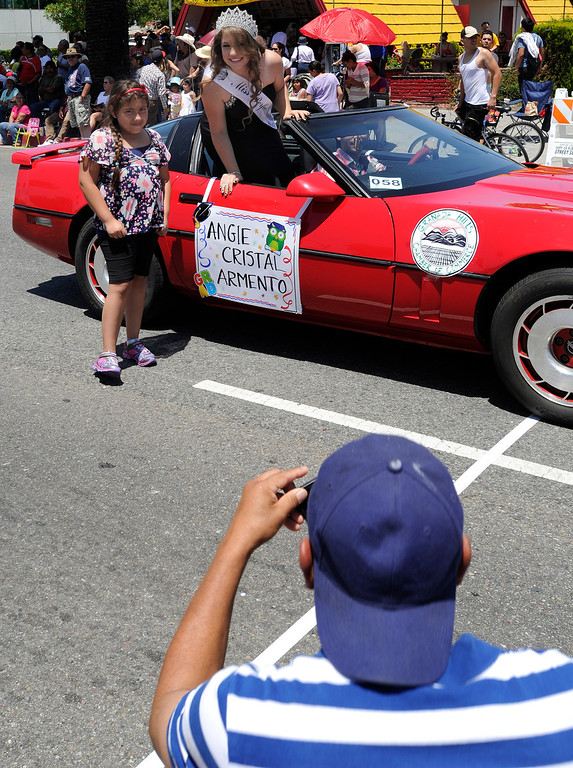 . Raul takes a photo of his daughter Alondra Gomez,9, who stands with Angie Cristal Armento who was riding in a Corvette. The Annual Canoga Park Memorial Day Parade marched down Sherman Way from Owensmouth east to Mason Street where it concluded at the First Baptist Church. Canoga park, CA 5/27/2013(John McCoy/LA Daily News)