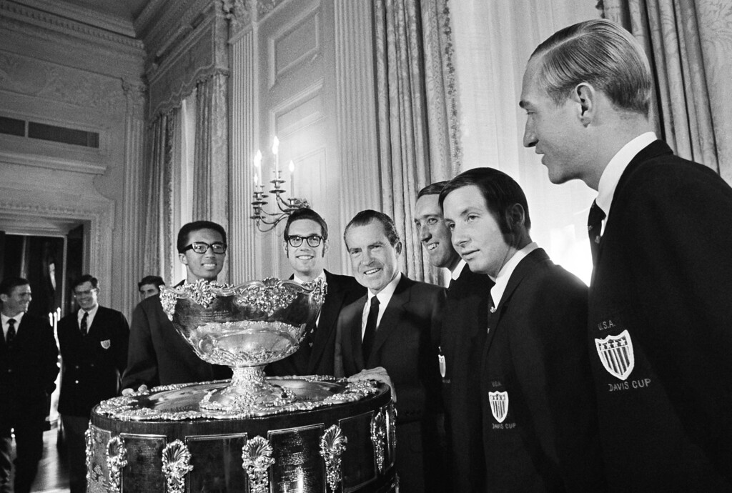 """. U.S. President Nixon bad one word for the huge trophy brought to the White House, Washington, Feb. 11, 1969 by the United States Davis Cup Tennis Team. It was \""""Wow\"""" The team members with Nixon are, from left: Arthur Ashe, Clark Grachner, Donald Bell and Bob Lutz. They were luncheon guests of Nixon. (AP Photo)"""