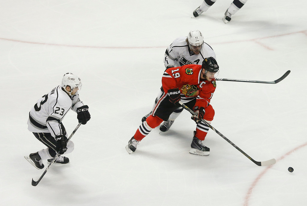 . Chicago Blackhawks center Jonathan Toews (19) maintains control of the puck against Los Angeles Kings right wing Dustin Brown (23) and Los Angeles Kings center Anze Kopitar (11) during the first period in Game 2 of an NHL hockey Stanley Cup Western Conference finals Sunday, June 2, 2013 in Chicago. (AP Photo/Charles Rex Arbogast)