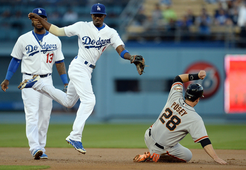 . The Giants\' Buster Posey #28 is out at 2nd as the Dodgers\'  Dee Gordon #9 jumps out of the way for a double play during their game at Dodger Stadium Friday, May 9, 2014. (Photo by Hans Gutknecht/Los Angeles Daily News)