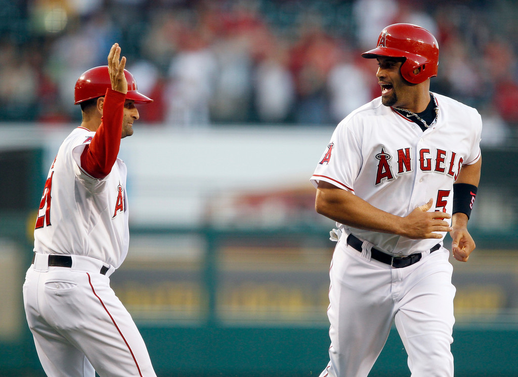. Los Angeles Angels\' Albert Pujols, right, yells out to third base coach Dino Ebel, left, after rounding third to score on a two-run home run by Angels\' Josh Hamilton  in the first inning against the Seattle Mariners during a baseball game Tuesday, May 21, 2013 in Anaheim.    (AP Photo/Alex Gallardo)