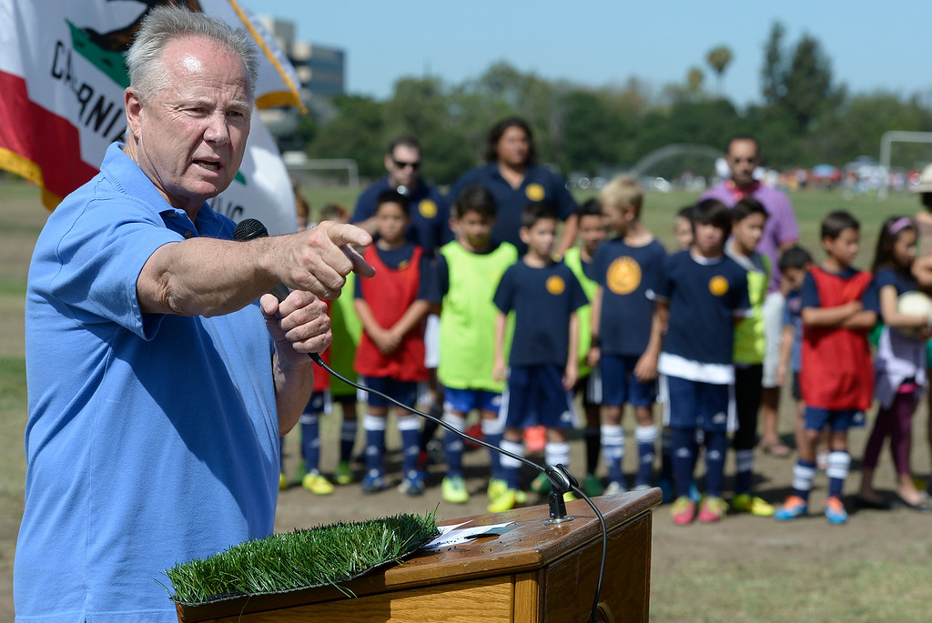 . Standing behind a sample of synthetic turf, while soccer players stand on dirt where grass should be, Councilmember Tom LaBonge talks about renovations. LaBonge joined the Los Angeles Department of Recreation and Parks, LA Bureau of Engineering and a group of young soccer players to break ground on three new synthetic turf soccer fields at the Van Nuys Sherman Oaks Park. The $2.7-million renovation will include synthetic fields that can be used year round. Also planned are new paved walkways and benches. Sherman Oaks, CA. 7/1022014(Photo by John McCoy Daily News)
