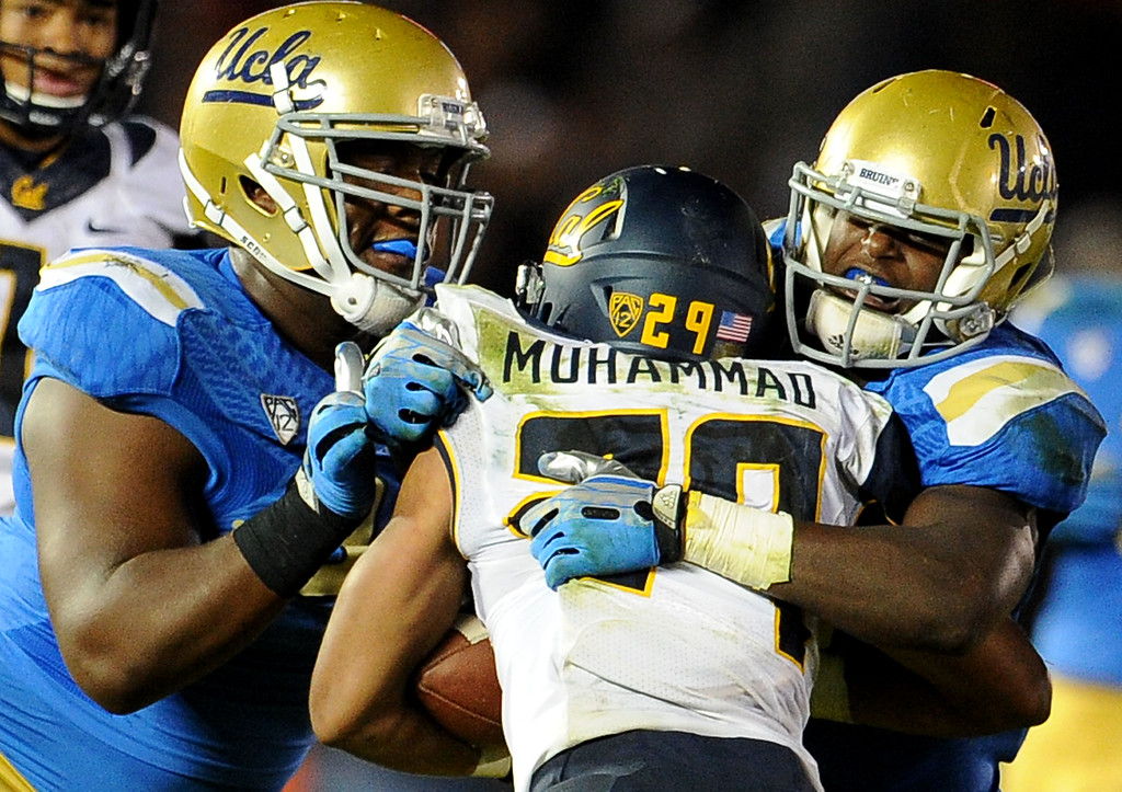. UCLA defense tackles California running back Khalfani Muhammad (29) for a loss of yards during the second half of their college football game in the Rose Bowl in Pasadena, Calif., on Saturday, Oct. 12, 2013.   (Keith Birmingham Pasadena Star-News)