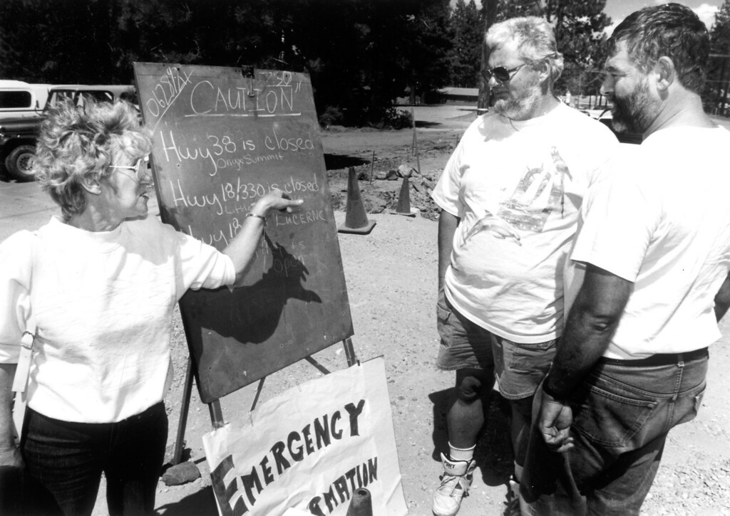 . June 28, 1992: Volunteer Sally Ehrheart shows stranded motorists Paul Bowers, left, and Charlie Painter the roads that were closed in the mountains.  Daily News file photo