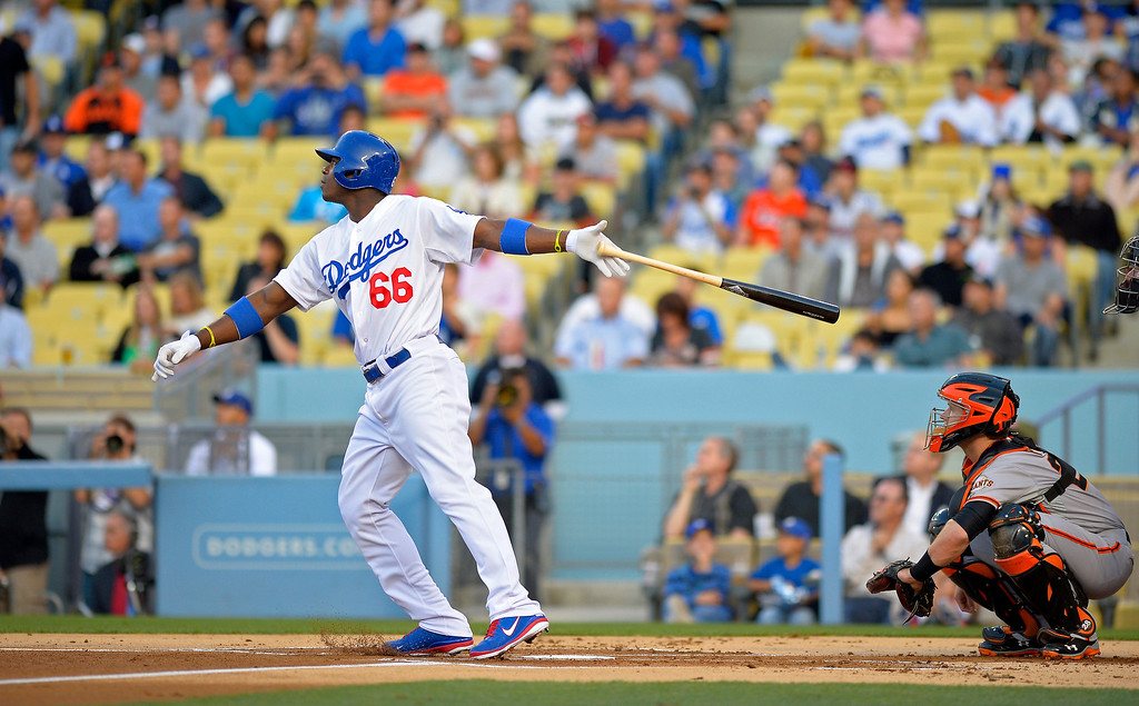 . Los Angeles Dodgers\' Yasiel Puig, left, hits a solo home run as San Francisco Giants catcher Buster Posey watches during the first inning of their baseball game, Monday, June 24, 2013, in Los Angeles. Dodgers won 3-1.   (AP Photo/Mark J. Terrill)