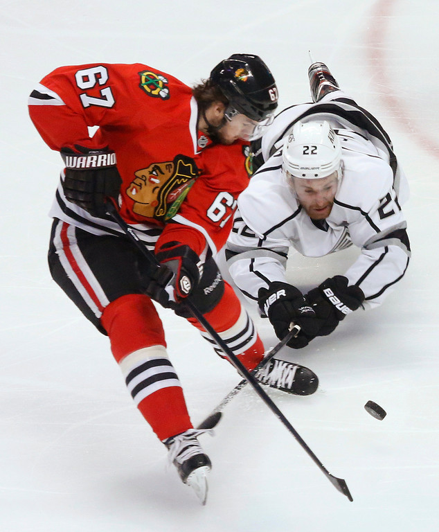 . Los Angeles Kings center Trevor Lewis (22) dives for the puck against Chicago Blackhawks center Michael Frolik (67) during the second period of Game 1 of the NHL hockey Stanley Cup Western Conference finals, Saturday, June 1, 2013, in Chicago. (AP Photo/Charles Rex Arbogast)