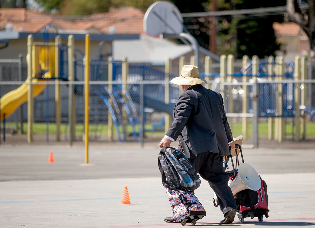 . Longden Elementary School officials pick up abandoned student backpacks after Los Angeles County Sheriff\'s deputies responded to a bomb threat at the Temple City, Calif. campus Sept. 25, 2013.  (Staff photo by Leo Jarzomb/San Gabriel Valley Tribune)