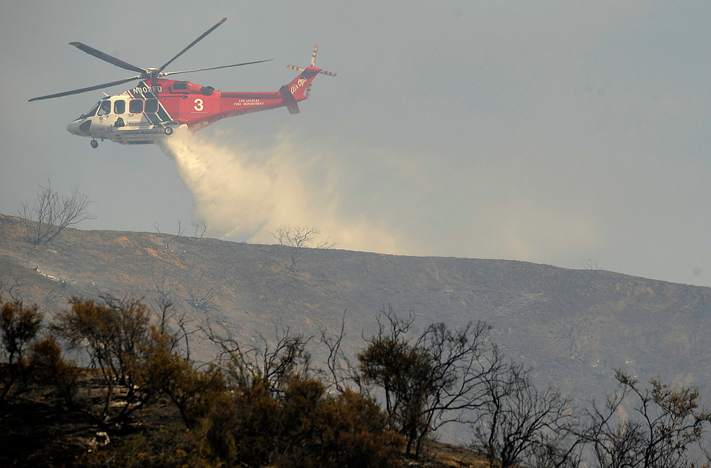 . A helicopter makes a water drop on the hillside behind the Self Realization Fellowship Glendale Temple on Chevy Chase.  A brush fire burned nearly 75 acres in an area north and east of the 134 and 2 freeways in Glendale. Residents on Easat Chevy Chase, east of the 2 freeway were evacuated as helicopters, hand crews and firefighters battled the fire that burned through the mountains and canyons. Glendale, CA 5/3/2013(John McCoy/Staff Photographer)