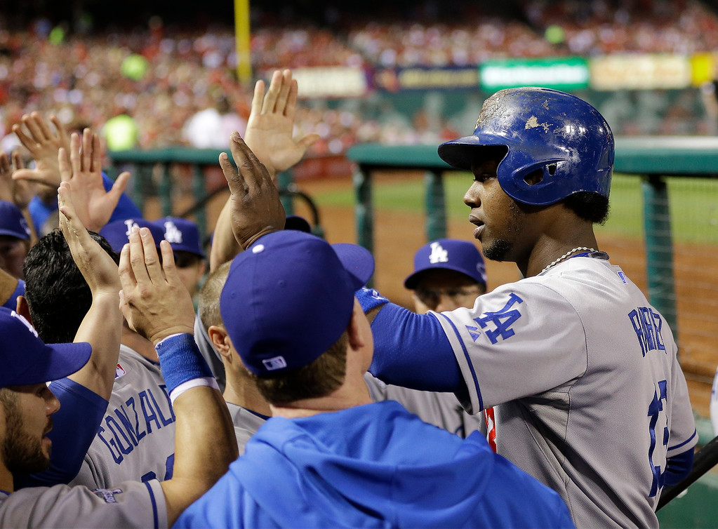 . Los Angeles Dodgers\' Hanley Ramirez is congratulated in the dugout after scoring during the third inning of Game 1 of the National League baseball championship series against the St. Louis Cardinals Friday, Oct. 11, 2013, in St. Louis. (AP Photo/David J. Phillip)