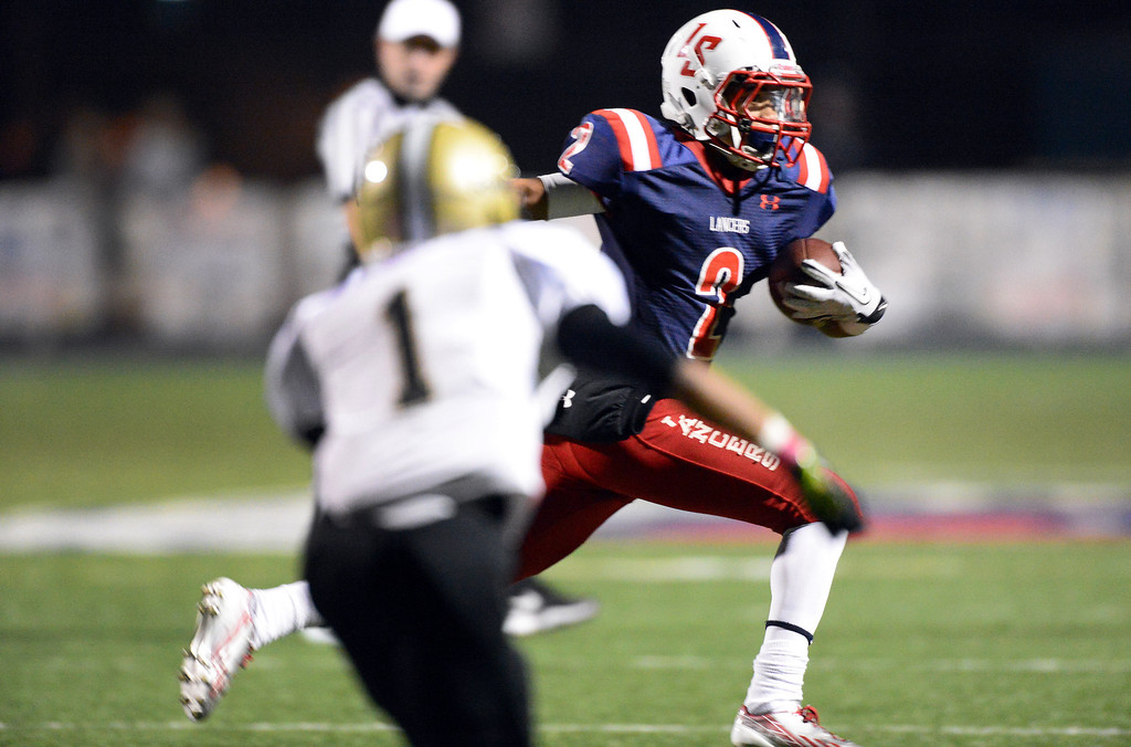 . La Salle\'s Bryce Harvey (2) gains yards as they play Bishop Montgomery during the first quarter in Friday night\'s football game at La Salle High School in Pasadena, October 25, 2013.  (Photo by Sarah Reingewirtz/Pasadena Star-News)