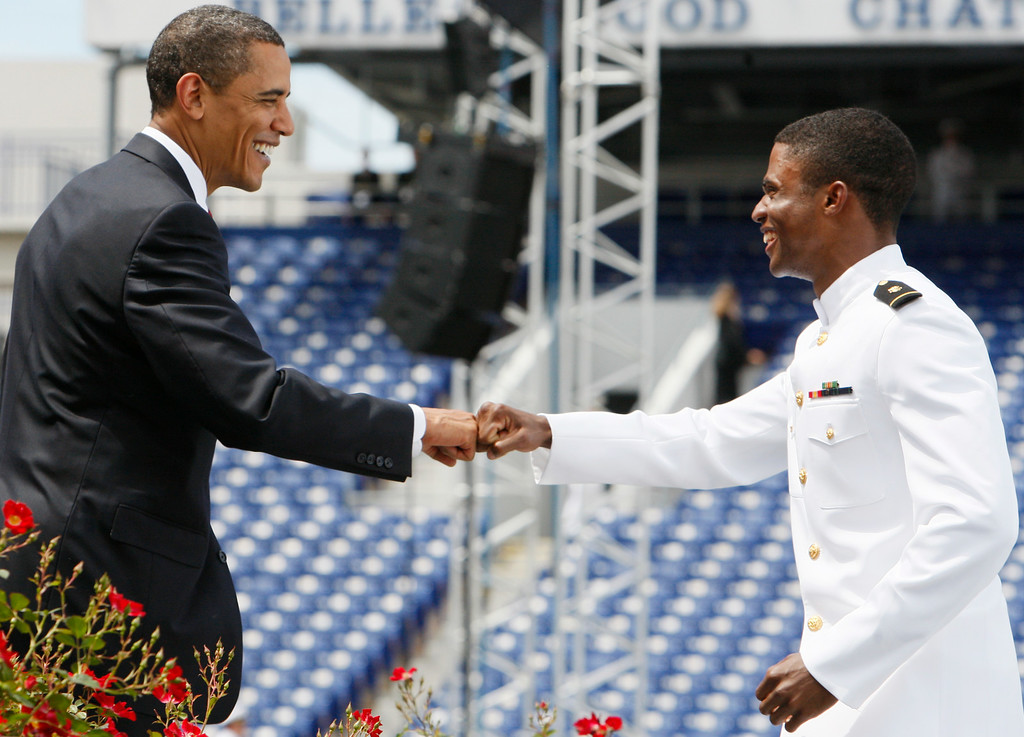 . In this May 22, 2009 file photo, President Barack Obama fist bumps Chauncy Lorrell Gray, from Chicago, as he approaches the stage to receive his diploma at the United States Naval Academy graduation ceremony in Annapolis, Md. The familiar knocking of knuckles spreads only one-twentieth the amount of bacteria that a handshake does, researchers report. That\'s better than a high-five, which still passes along less than half the amount as a handshake. (AP Photo/Charles Dharapak, File)