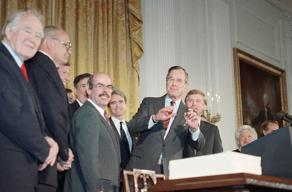. U.S. President George H. Bush gestures after he signed the Clean Air Act of 1990, Thursday, Nov. 15, 1990 in the White House East Room in Washington.  At the ceremony from left are Sen. John Chafee, R-RI., Rep. Henry Waxman, D-Calif.; Environmental Protection Agency Administrator William Riley; Bush and Vice President Dan Quayle. (AP Photo/Charles Tasnadi)