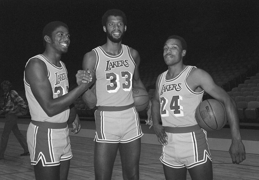 """. New Los Angeles Laker Earvin \""""Magic\"""" Johnson, left, former Michigan State champion, greets Lakers veteran Kareem Abdul-Jabbar (33) and Ron Boone (24) during Lakers photo day at the Forum at Los Angeles, Sept. 15, 1979.  Johnson was the first-round, first pick in the 1979 player draft, after leading Michigan State to the NCAA championship.  (AP Photo/Nick Ut)"""