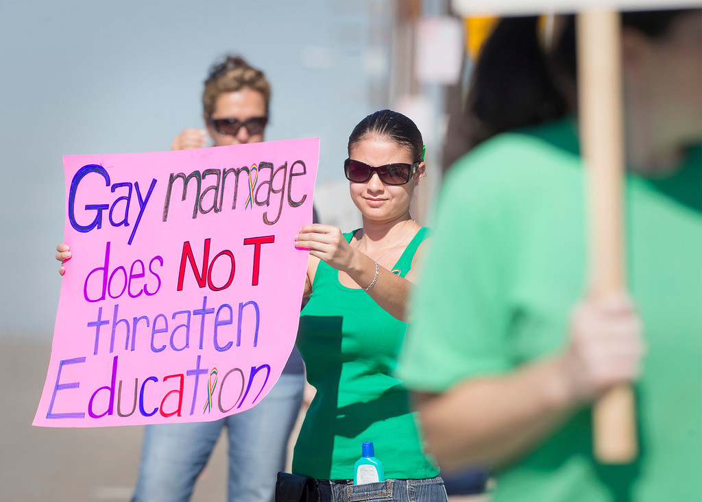 . St. Lucy\'s Priory High School alum Melissa Magdaleno, 24, protests the dismissal of longtime teacher Ken Bencomo at the Glendora, Calif. campus August 8, 2013.  Bencomo was  terminated from the all-girls private parochial school after a photo of his marriage to his same-sex partner was published in a local newspaper.  (SGVN/Staff photo by Leo Jarzomb)