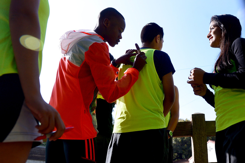 . Elite marathon runner Julius Keter, of Kenya, signs a jerseys as elite marathon athletes visit with students of Students Run LA program during a training run for the LA Marathon at Griffith Park in Los Angeles Friday, March 7, 2014. The students will also be running Sunday\'s marathon. (Photo by Sarah Reingewirtz/Pasadena Star-News)