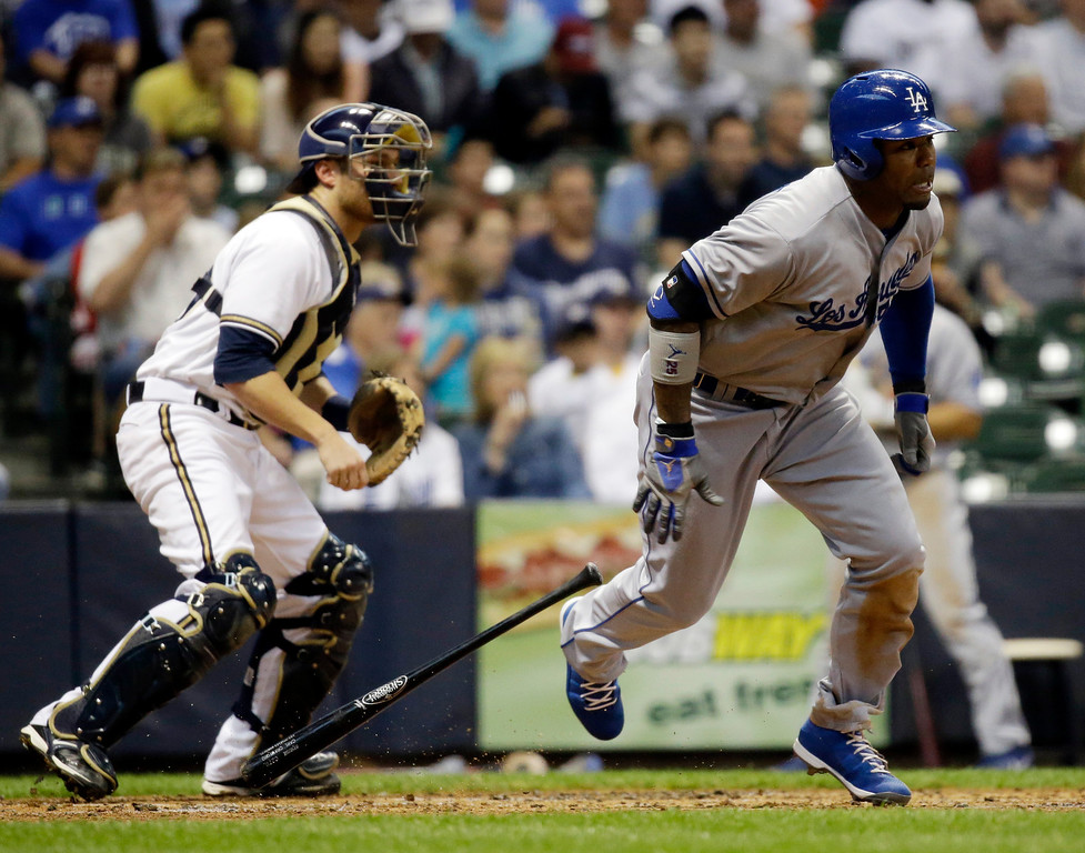 . Milwaukee Brewers catcher Jonathan Lucroy watches as Los Angeles Dodgers\' Carl Crawford hits a two-run single during the second inning of a baseball game against the Milwaukee Brewers Wednesday, May 22, 2013, in Milwaukee. (AP Photo/Morry Gash)