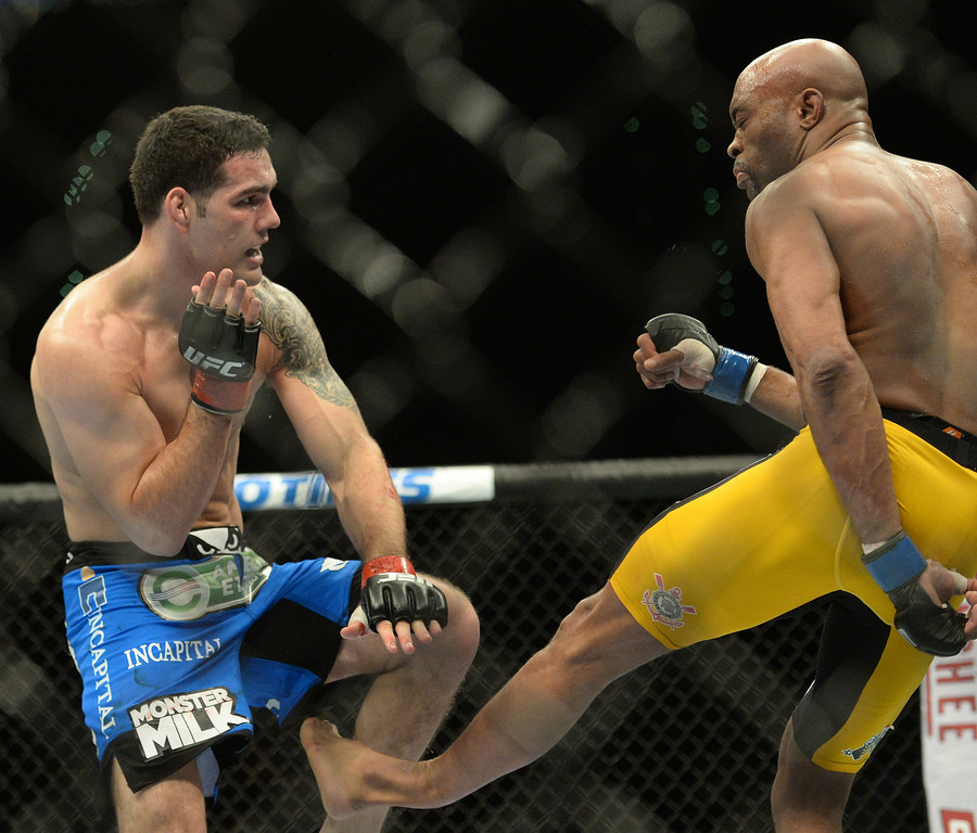 . Champion Chris Weidman, red, checks a leg kick by  Anderson Silva, blue, breaking Silva\'s leg during their  Middleweight Championship bout during UFC 168 at the MGM Grand in Las Vegas Saturday, December 28, 2013. Weidman won due to injury to Silva. (Photo by Hans Gutknecht/Los Angeles Daily News)