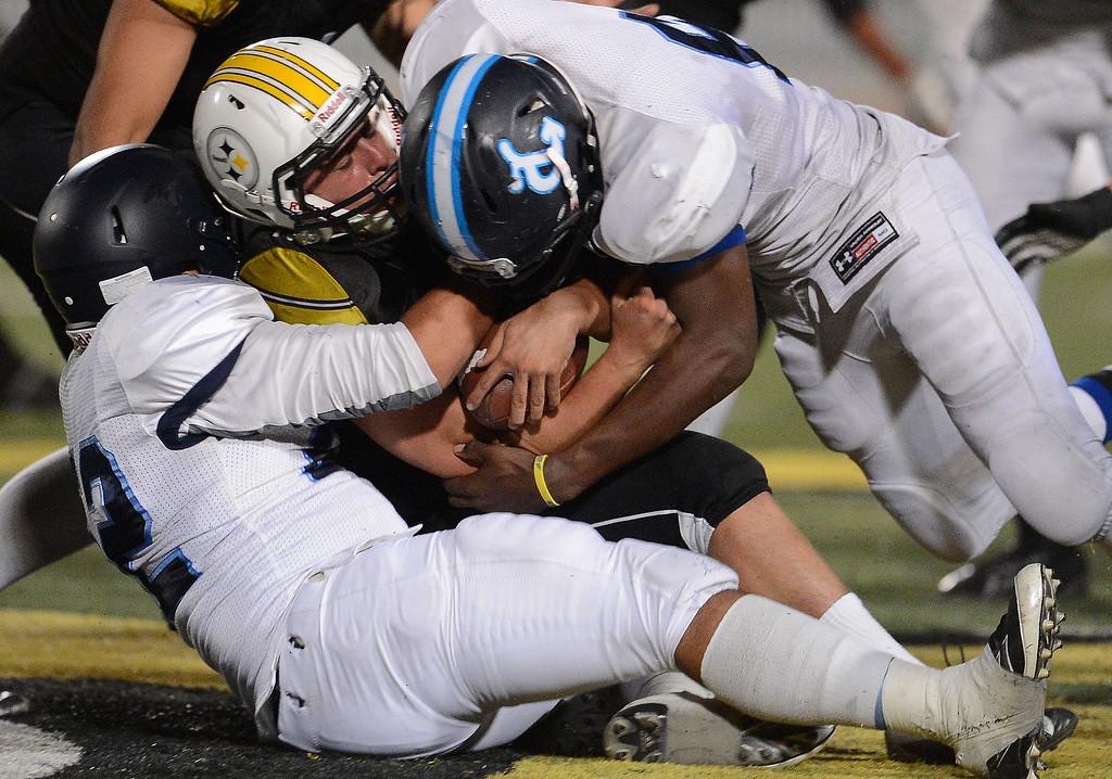 . Duarte defense tackles Bassett quarterback Nicolas Colmenero (10) for a loss of of yards in the first half of a prep football game at Bassett High School in La Puente, Calif., on Friday, Nov. 1, 2013.    (Keith Birmingham Pasadena Star-News)