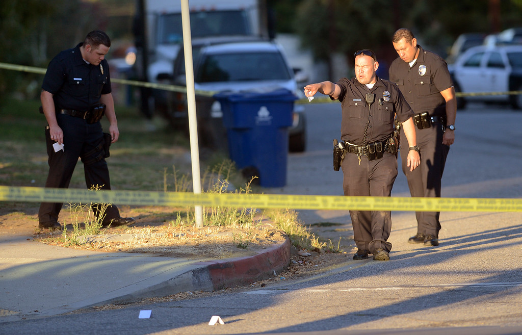 . LAPD officers search for evidence near the scene of a shootout with robbery suspects who engaged officers in a pursuit, shootout and manhunt in Reseda, Ca July 8, 2013.  Both suspects were apprehended after a search along Tampa Ave near Strathern St. Monday evening.(Andy Holzman/Los Angeles Daily News)