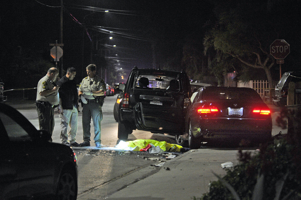 . This image provided by the Santa Barbara Independent shows a body covered on the ground after a mass shooting near the campus of the University of Santa Barbara in Isla Vista, Calif., Friday, May 23, 2014. A drive-by shooter went on a rampage near the Santa Barbara university campus that left seven people dead, including the attacker, and others wounded, authorities said Saturday. (AP Photo/Santa Barbara Independent, Paul Wellman)