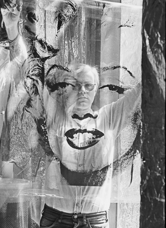 ". In this 1964 photo provided by Allen Cooper Enterprises, artist Andy Warhol holds an unrolled acetate of ""Marilyn\"" in his New York studio called \""The Factory.\"" The photo was featured in an exhibit entitled: \""Before They Were Famous: Behind the Lens of William John Kennedy,\"" which ran through April 29, 2012 at the Site/109 gallery in New York. (AP Photo/William John Kennedy via Allen Cooper Enterprises)"