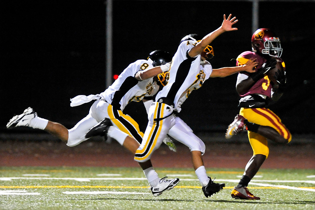 . LOS ANGELES - 10/04/2013 - (Mark Savage) Fairfax player #9 Kenny Allen scores a touchdown in the fourth quarter despite the defensive efforts of San Pedro players #8 Albert Martinez and #13 Chris Lauro. Fairfax High School plays San Pedro High School at Fairfax High School.