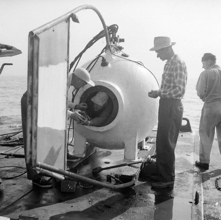 . Diver Otis Barton, who hopes to break his own record for descents into the sea, leans from the steel diving bell as he prepared for a practice dive, Sept. 24, 1952, on Catalina Island, Calif. Talking to Barton at left is Dr. Maurice Nelles, his technical advisory. At right is Perry Stille, electronic communications expert. The descents are made from a barge off the island  (AP Photo)