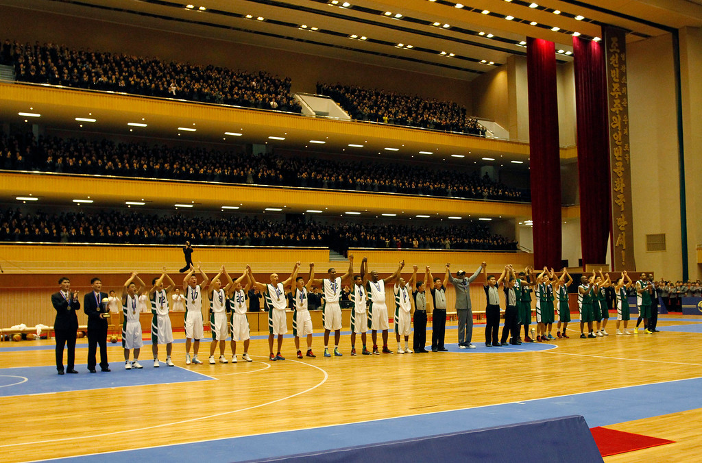 . U.S. and North Korean basketball players raise their hands to the crowd after an exhibition game held at an indoor stadium in Pyongyang, North Korea on Wednesday, Jan. 8, 2014. Former NBA star Dennis Rodman came to the North Korean capital with a team of U.S. basketball stars for an exhibition game on the birthday of North Korean leader Kim Jong Un. (AP Photo/Kim Kwang Hyon)