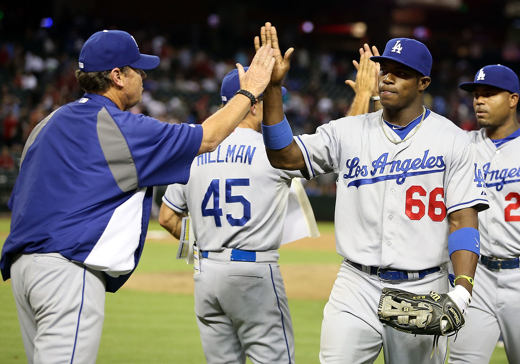 . PHOENIX, AZ - JULY 08:  Yasiel Puig #66 of the Los Angeles Dodgers high fives pitching coach Rick Honeycutt after defeating the Arizona Diamondbacks in the MLB game at Chase Field on July 8, 2013 in Phoenix, Arizona. The Dodgers defeated the Diamondbacks 6-1.  (Photo by Christian Petersen/Getty Images)