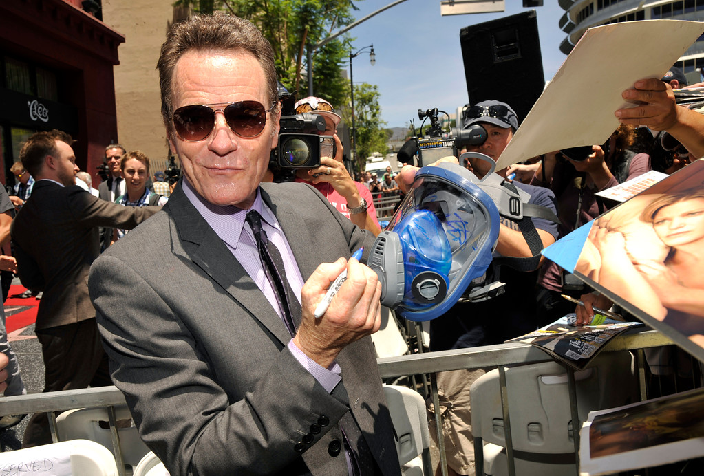 ". Actor Bryan Cranston, who plays high school chemistry teacher and methamphetamine manufacturer Walter White on the television series ""Breaking Bad,\"" signs a gas mask for a fan after receiving a star on the Hollywood Walk of Fame on Tuesday, July 16, 2013 in Los Angeles. (Photo by Chris Pizzello/Invision/AP)"