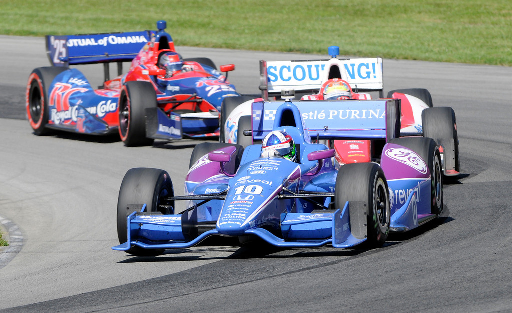 . Dario Franchitti, of Scotland, leads Justin Wilson, of England, and Marco Andretti through a corner during the Honda Indy 200 at Mid-Ohio Sports Car Course in Lexington, OH Sunday, Aug. 4, 2013. (AP Photo/Tom E. Puskar)