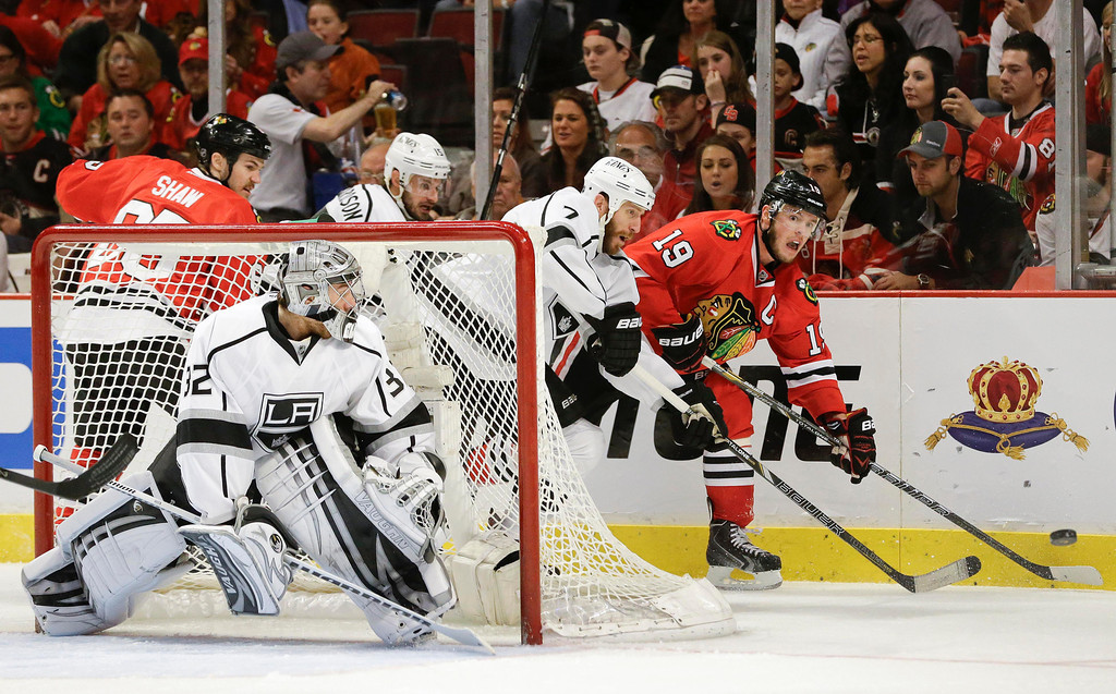 . Chicago Blackhawks center Jonathan Toews (19) passes off the puck against Los Angeles Kings defenseman Rob Scuderi (7) as goalie Jonathan Quick (32) defends during the second period of Game 2 of an NHL hockey Stanley Cup Western Conference finals, Sunday, June 2, 2013, in Chicago. (AP Photo/Nam Y. Huh)