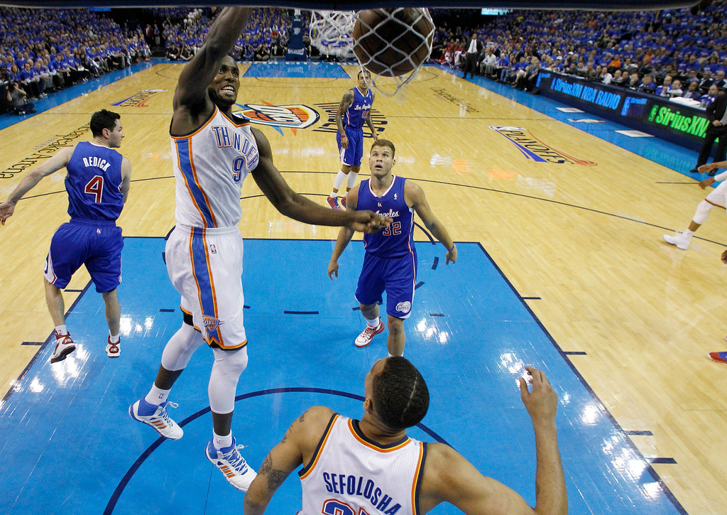 . Oklahoma City Thunder forward Serge Ibaka (9) dunks in front of Los Angeles Clippers forward Blake Griffin (32) in the first quarter of Game 1 of the Western Conference semifinal NBA basketball playoff series in Oklahoma City, Monday, May 5, 2014. (AP Photo/Sue Ogrocki)