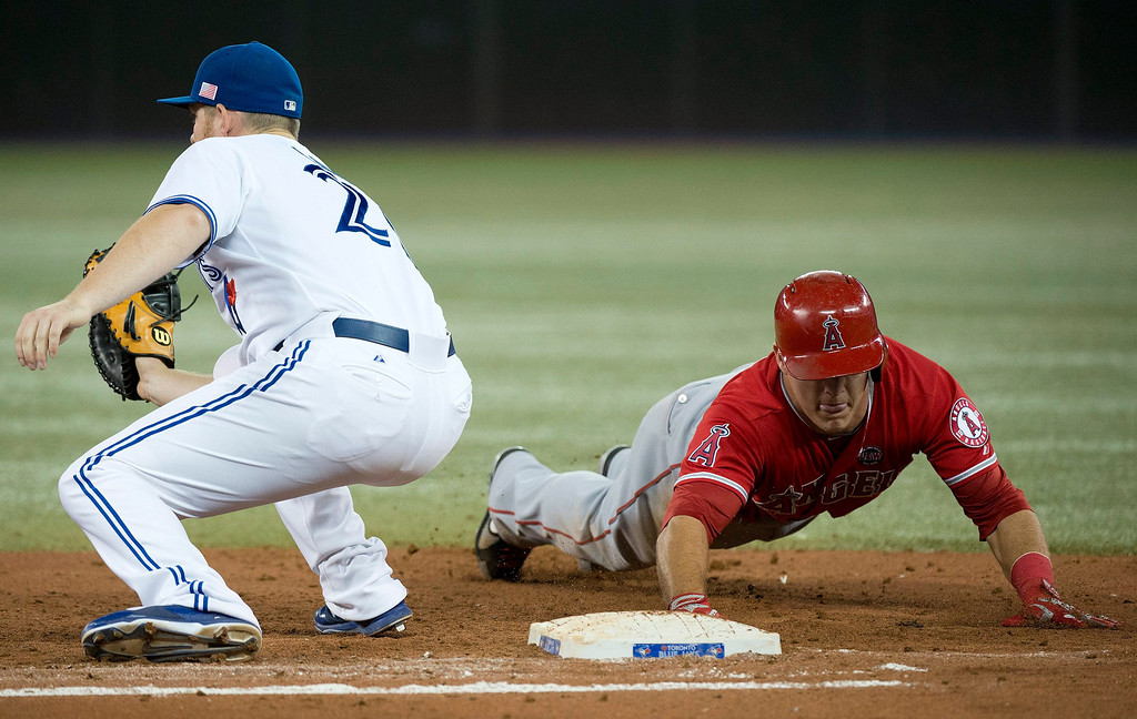 . Toronto Blue Jays first baseman Adam Lind, left, tries to tag out Los Angeles Angels\' Mike Trout, right, at first base after Trout was nearly caught leading off during fourth-inning AL baseball game action in Toronto, Wednesday, Sept. 11, 2013. (AP Photo/The Canadian Press, Nathan Denette)