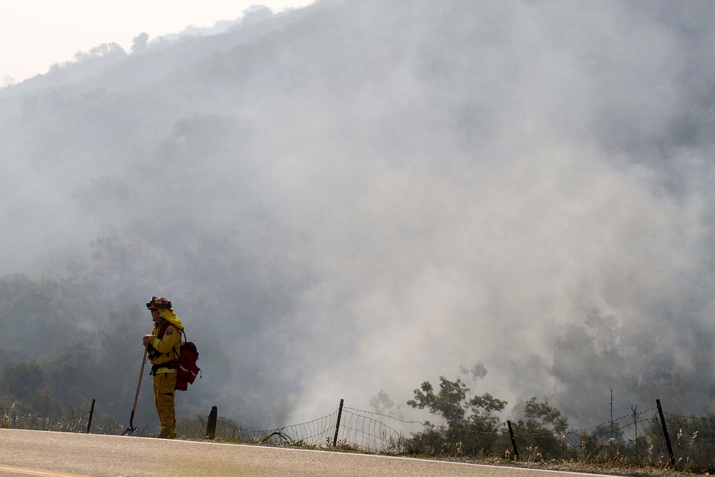 . A firefighter stands watch as the smoke rises from the burnt area in Hidden Valley, Calif., Saturday, May 4, 2013. High winds and withering hot, dry air was replaced by the normal flow of damp air off the Pacific, significantly reducing fire activity.  (AP Photo/Ringo H.W. Chiu)