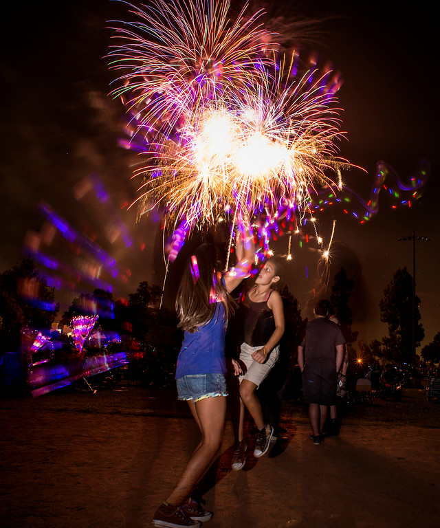 . Cousins Riley Vega, 9, and Lenise De La Torre, 8, both of Buena Park, play with glow sticks during La Mirada\'s annual fireworks show Thursday night, July 3, 2014 at La Mirada Regional Park. (Photo by Sarah Reingewirtz/Pasadena Star-News)