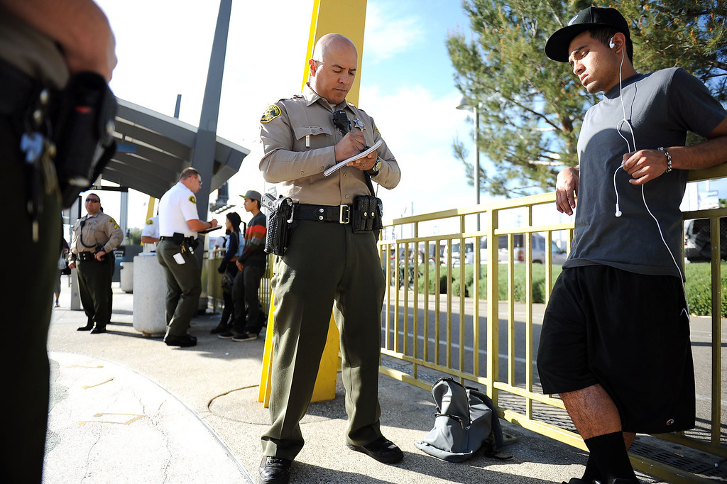 . LA County Sheriff deputy Carlos Valencia issues a fare evasion citation during an Orange Line fare enforcement operation at the Van Nuys Orange Line Station February 25, 2014.  Officials from Metro and the Los Angeles Sheriff\'s Department Transit Services Bureau announced a new two-pronged effort to cut down on fare-evaders on the Orange Line by improving communications and beefing up enforcement.(Andy Holzman/Los Angeles Daily News)