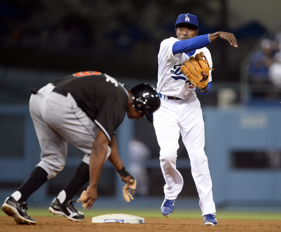 . Dee Gordon #9 of the Los Angeles Dodgers completes a double play in front of Juan Pierre #9 of the Miami Marlins as Chris Coghlan #8 scores to take a 5-3 lead during the seventh inning at Dodger Stadium on May 10, 2013 in Los Angeles, California.  Marlins won 5-4.   (Photo by Harry How/Getty Images)
