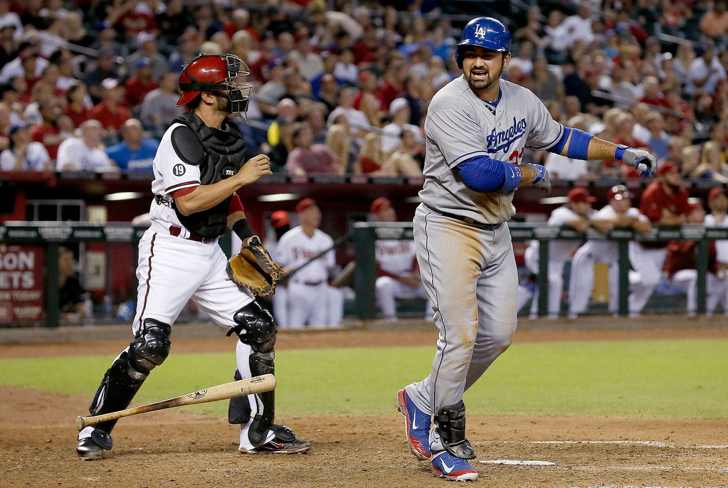 . Los Angeles Dodgers\' Adrian Gonzalez, right, slams his bat down after flying out to center field as Arizona Diamondbacks\' Wil Nieves looks back at the infield in the eighth inning of a baseball game on Monday, Sept. 16, 2013, in Phoenix.  The Diamondbacks defeated the Dodgers 2-1. (AP Photo/Ross D. Franklin)